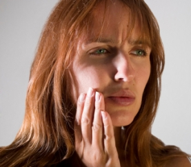 A photo of a woman with a toothache requiring an emergency dentist.