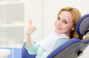 A woman giving a thumbs up in a dental chair