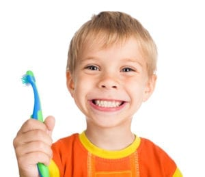 a boy smiling and holding a tooth brush