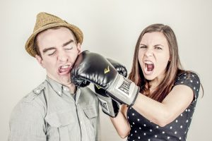 Woman hitting man in jaw wearing boxing glove
