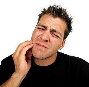 Man holding his cheek while in pain and in need of an emergency dentist